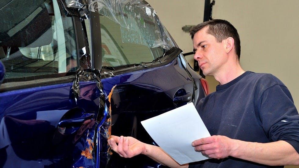 Expert automobile inspectant les portieres d'une automobile