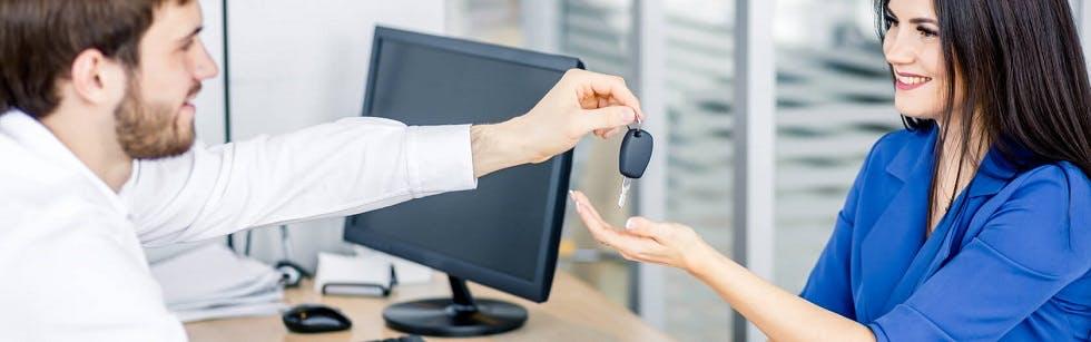 Conductrice recevant ses clés de voiture après avoir signé le bon de commande