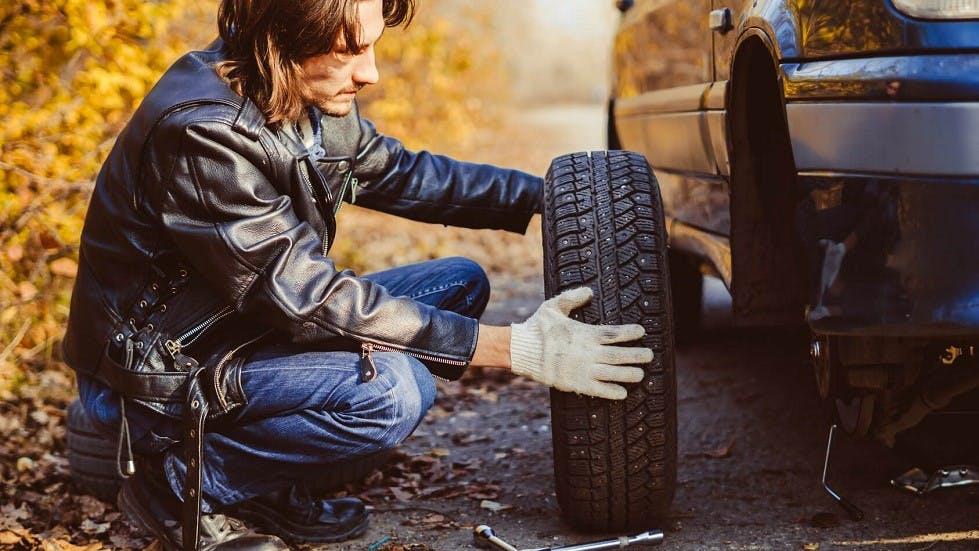 Usager changeant un pneu a crampons sur son vehicule