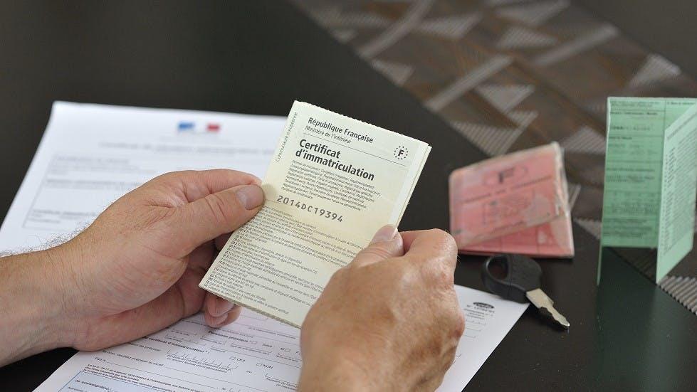 Usager de la route lisant les documents administratifs de son vehicule
