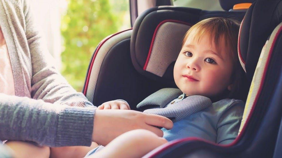 Mere de famille attachant son enfant dans un siege auto