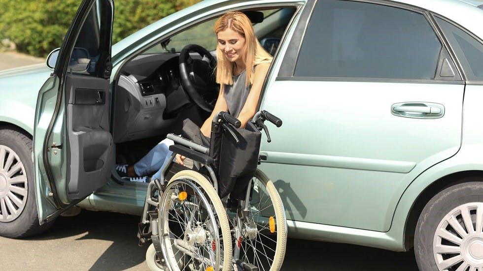 Automobiliste handicapee s'installant au volant de sa voiture