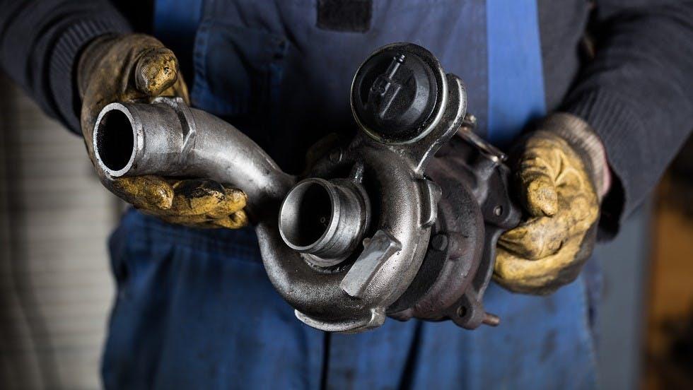 Garagiste retirant un turbocompresseur encrasse