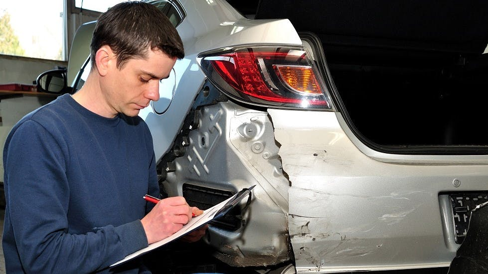 Expert realisant une expertise sur une automobile accidentee