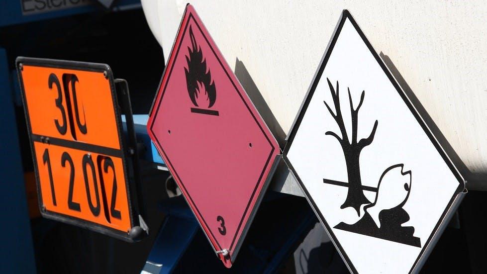 Plaque orange accompagnee de panneaux inflammable et polluant