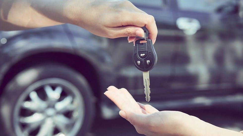 Conducteur tendant la cle de son vehicule a la nouvelle proprietaire