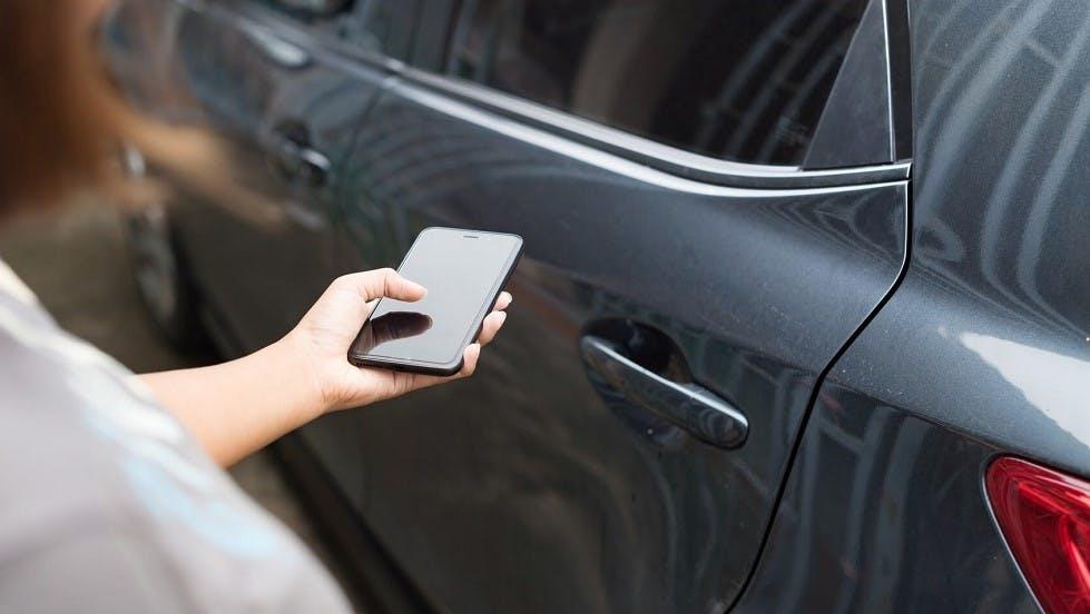 Conductrice utilisant son smartphone pour deverouiller un vehicule