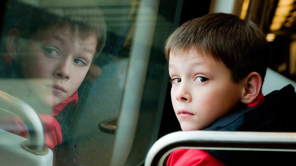 Reflet d'un enfant dans la vitre d'un bus