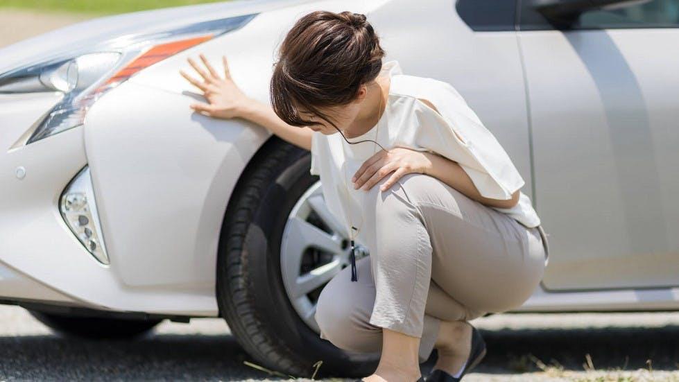 Conductrice verifiant l'etat de ses pneus arriere