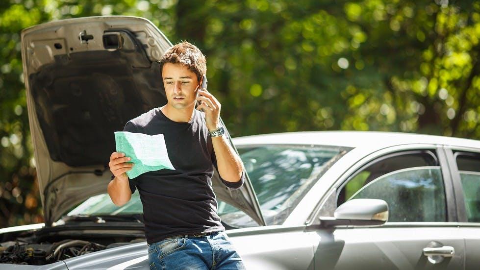 Jeune conducteur en panne appelant son assureur