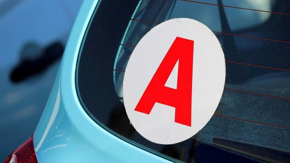 Disque de jeune conducteur appose sur une automobile bleue