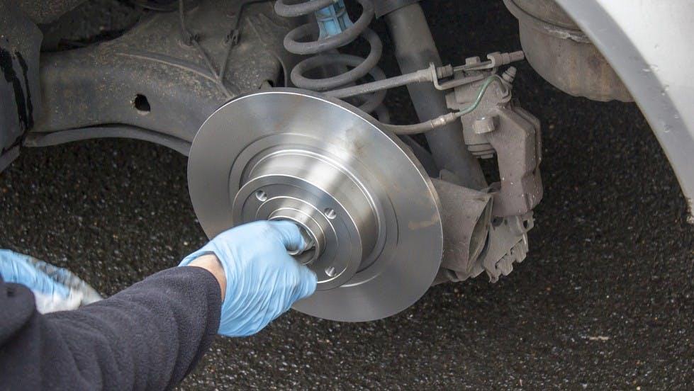 Garagiste nettoyant et changeant les freins d'une automobile
