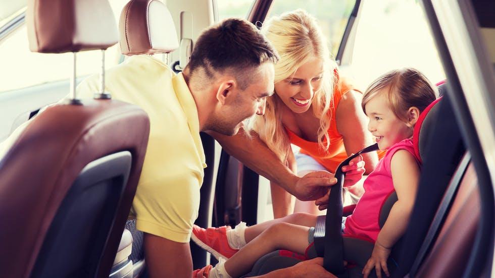 Parents qui installent un enfant dans son siège auto