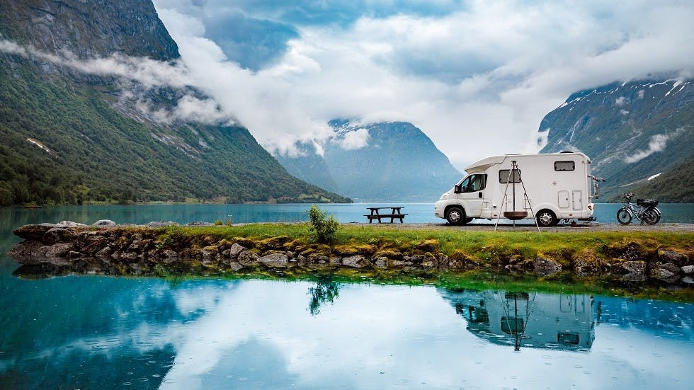 Camping-car devant un lac et des montagnes