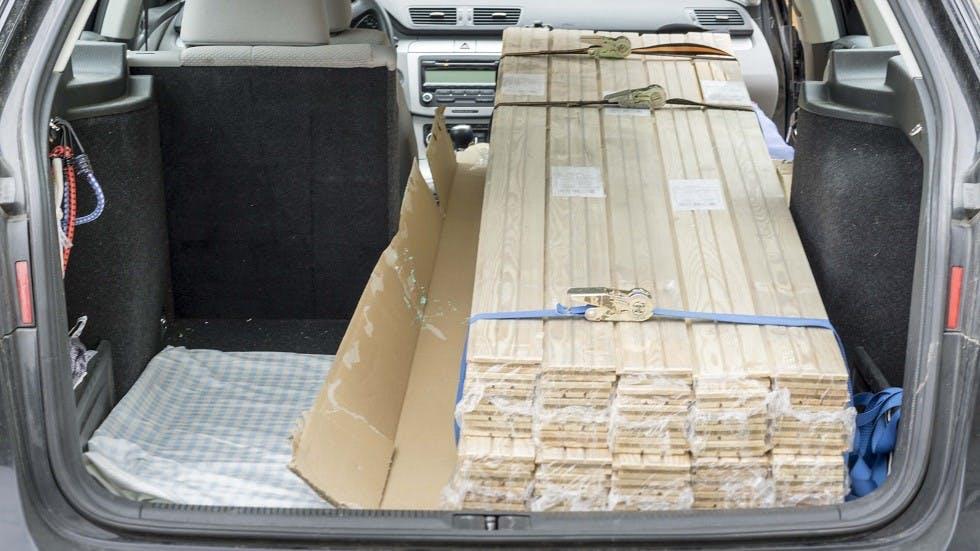 Automobile transportant un chargement de bois encombrant