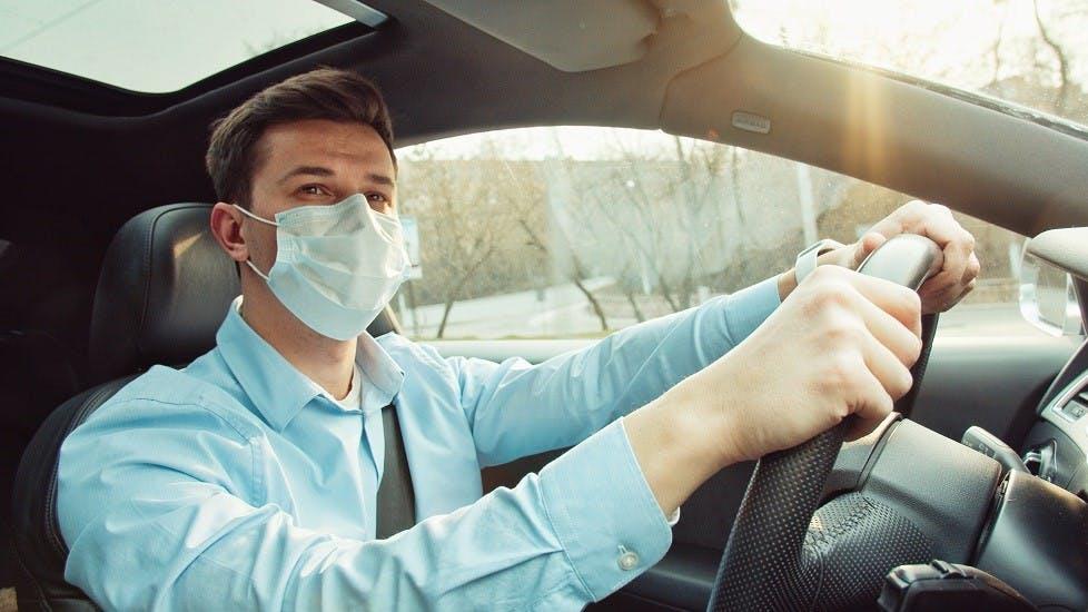 Automobiliste portant un masque jetable