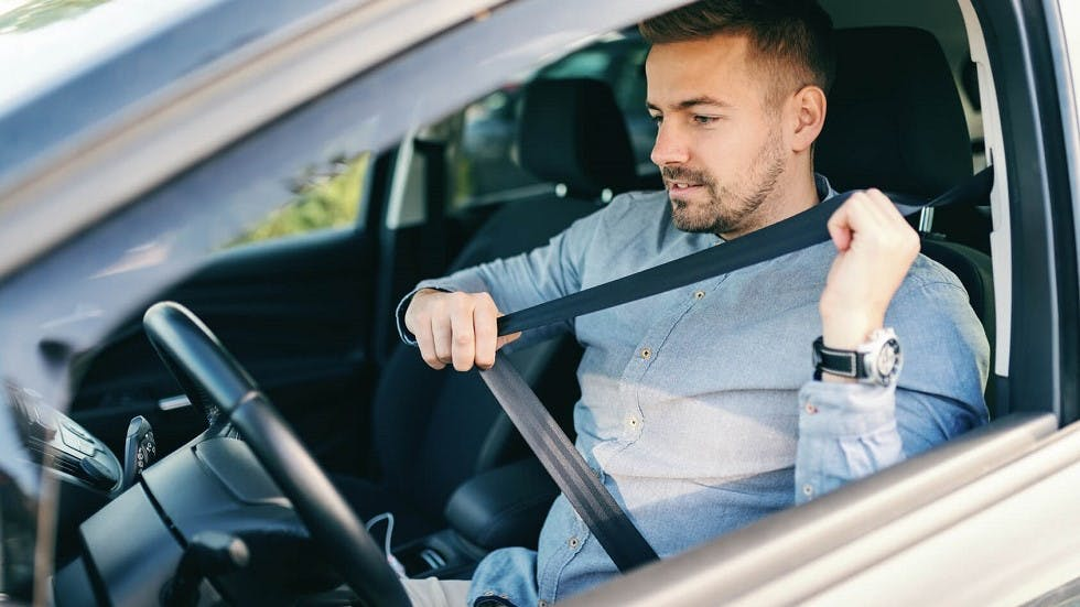 Automobiliste attachant sa ceinture de securite