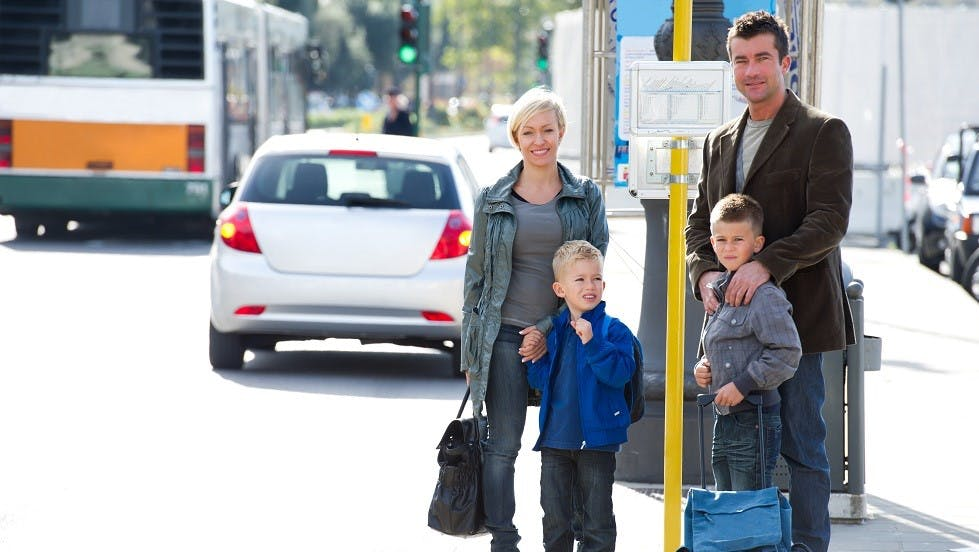 Enfants et parents attendant l'arrivee d'un bus scolaire