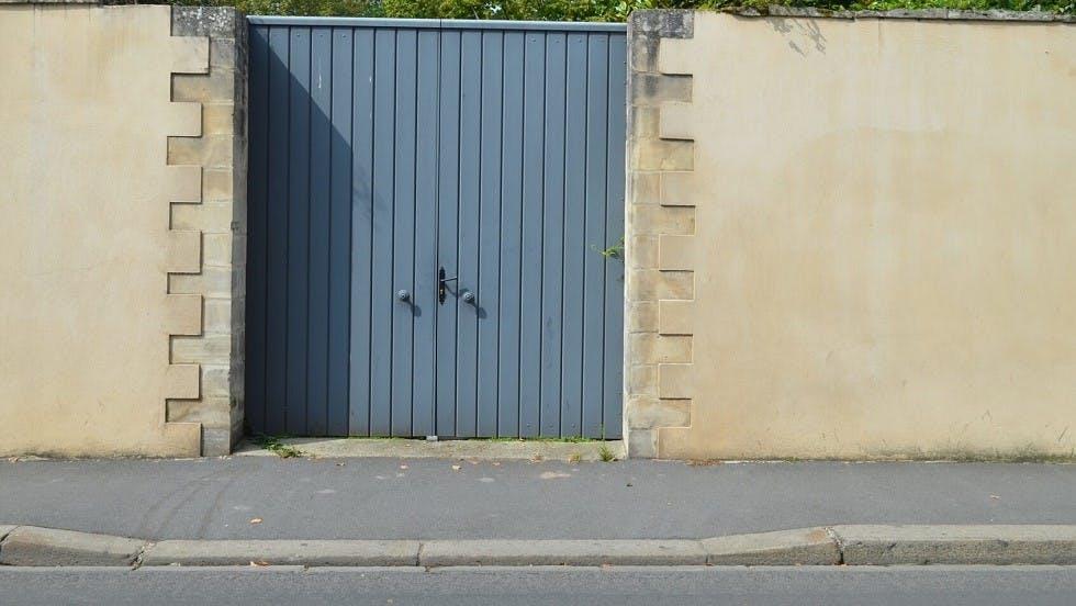 Entree carrossable devant un portail bleu