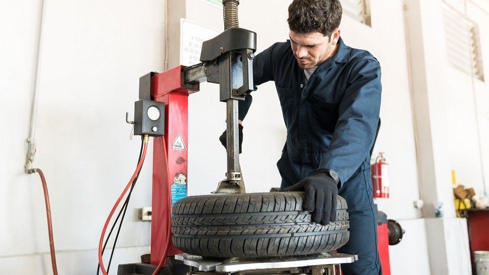 Garagiste utilisant un demonte-pneu pour remplacer un pneumatique