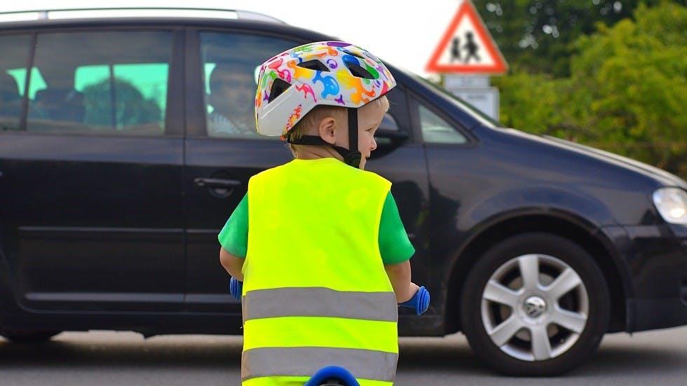 Enfant s'appretant a traverser devant un panneau de danger de traversee d'enfants