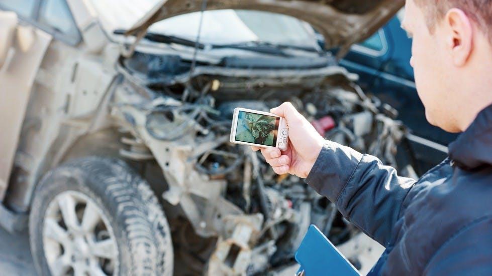 Expert automobile prenant une photo d'un vehicule economiquement irreparable