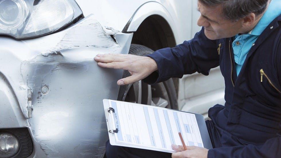 Expert verifiant les degats sur une auto suite a un accident