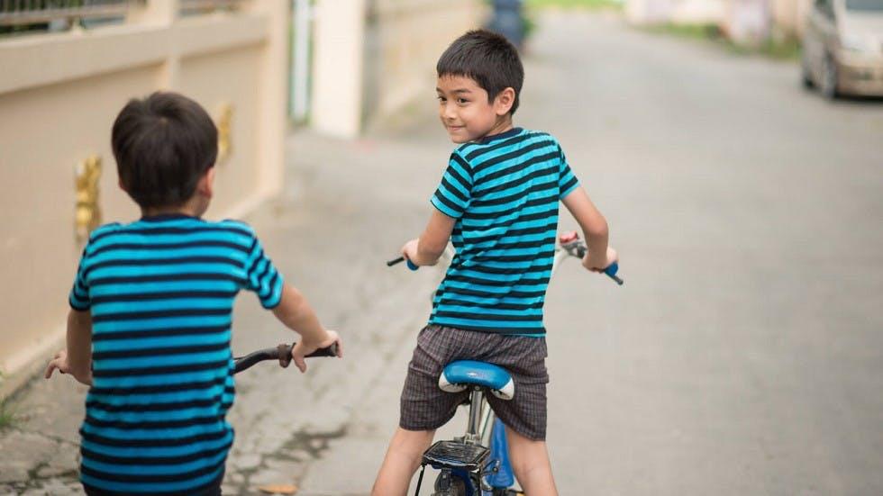 Enfants a velo seuls dans une ruelle