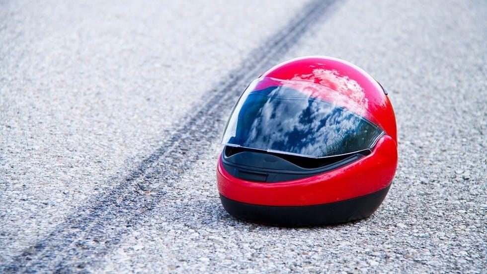 Casque de moto a cote de la trace de freinage d'une moto