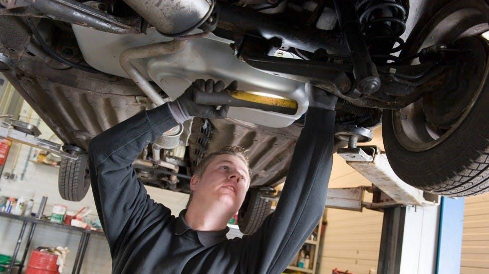 Garagiste inspectant des roues directrices