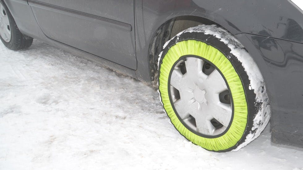 Chaine a neige textile installee sur le pneu d'un vehicule