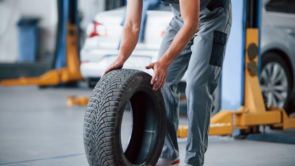 Garagiste transportant un pneu neuf