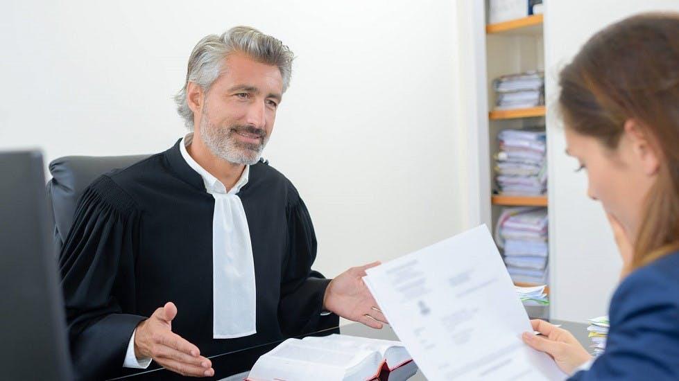 Avocat presentant une decision de justice a une assuree auto