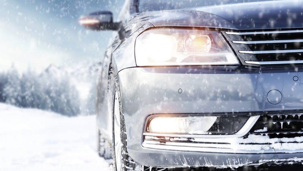 Feux d'une automobile circulant sous la neige