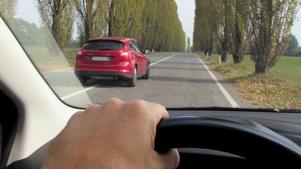 Automobile rouge chevauchant une ligne blanche