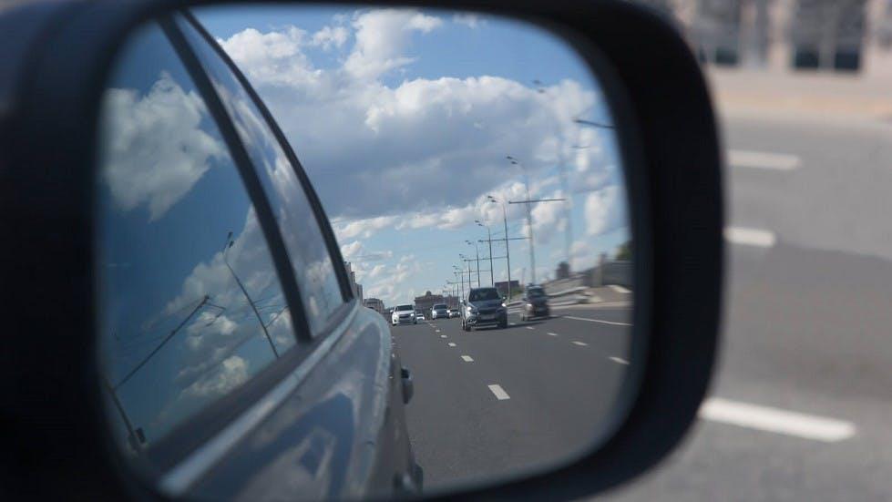Nombreuses automobiles apparaissant dans le reflet d'un retroviseur