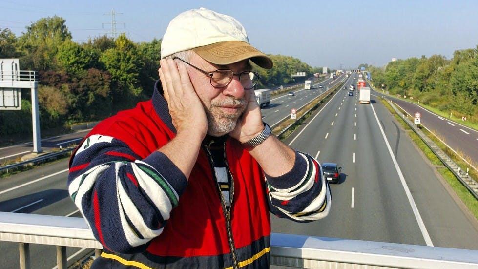 Pieton subissant une nuisance sonore pres d'une autoroute