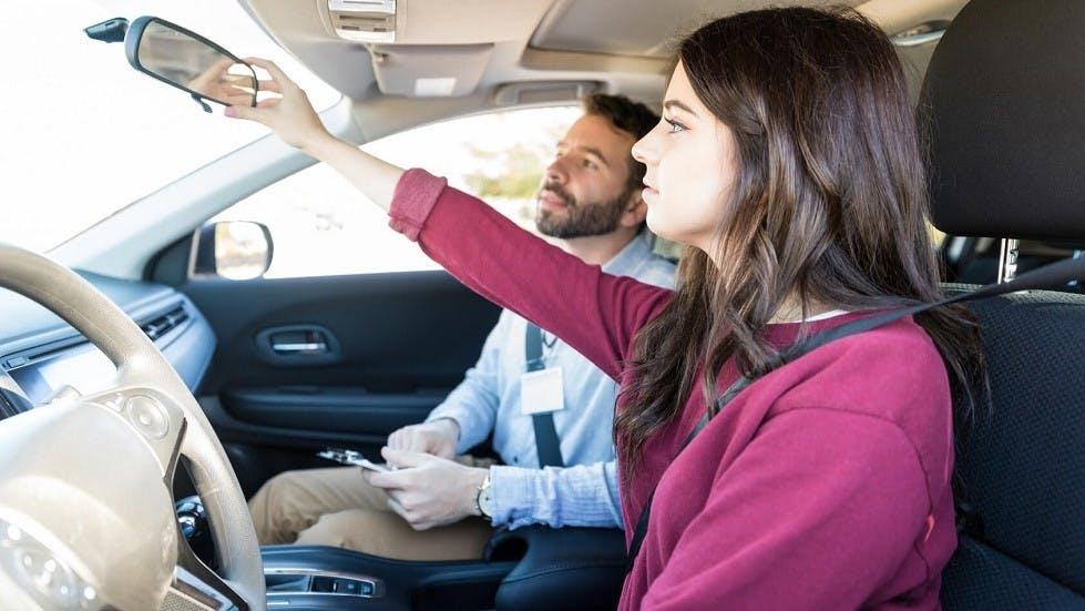 Candidate se formant pour l'examen du permis de conduire reglant son retroviseur