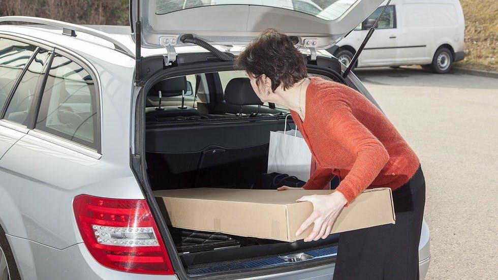 Conductrice faisant entrer un carton volumineux dans son coffre