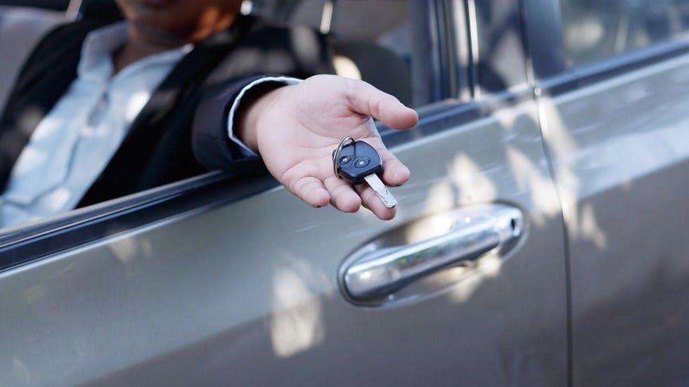 Automobiliste tendant la cle de son vehicule