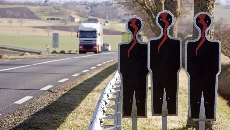 Groupe de silhouettes noires au bord d'une route