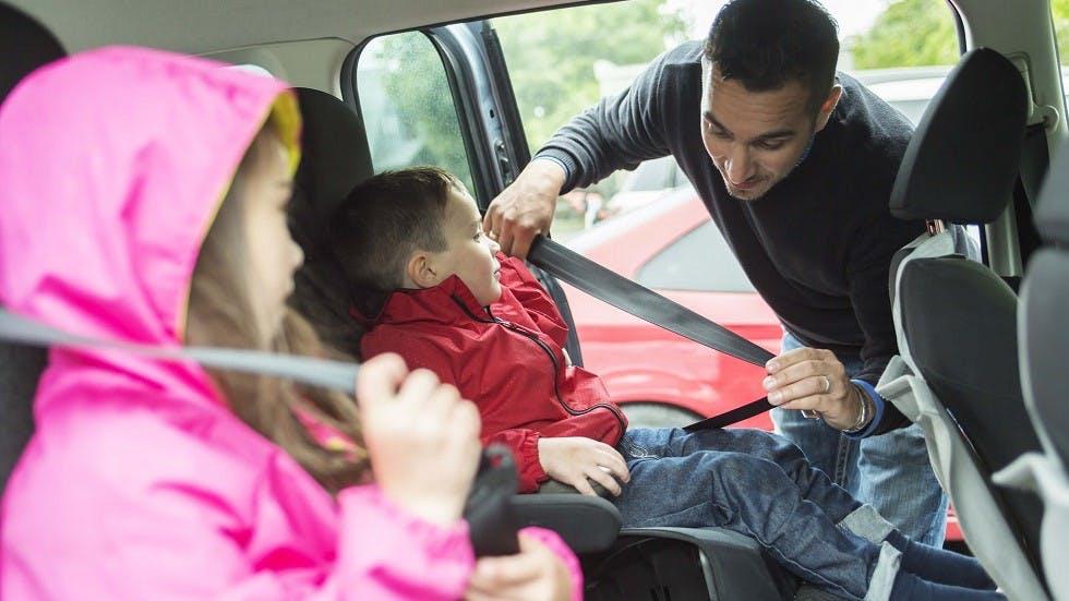 Pere de famille attachant la ceinture de securite de ses enfants