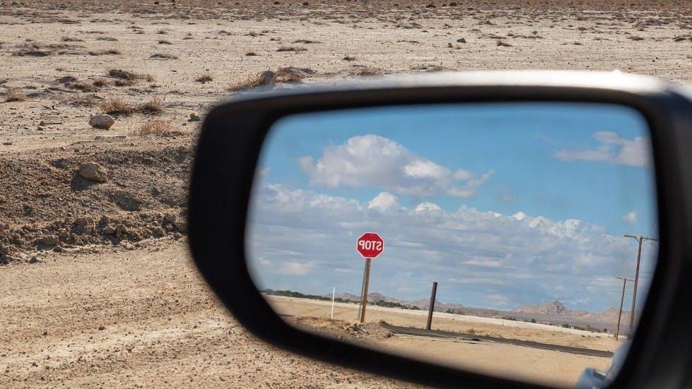 Panneau STOP visible dans le retroviseur d'une automobile