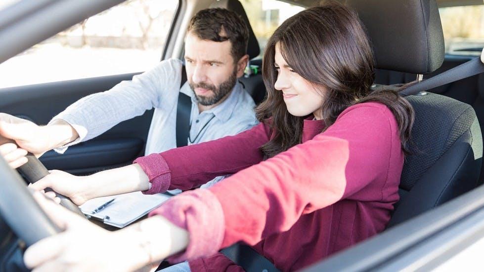 Examinateur du permis de conduire attrapant le volant d'une candidate