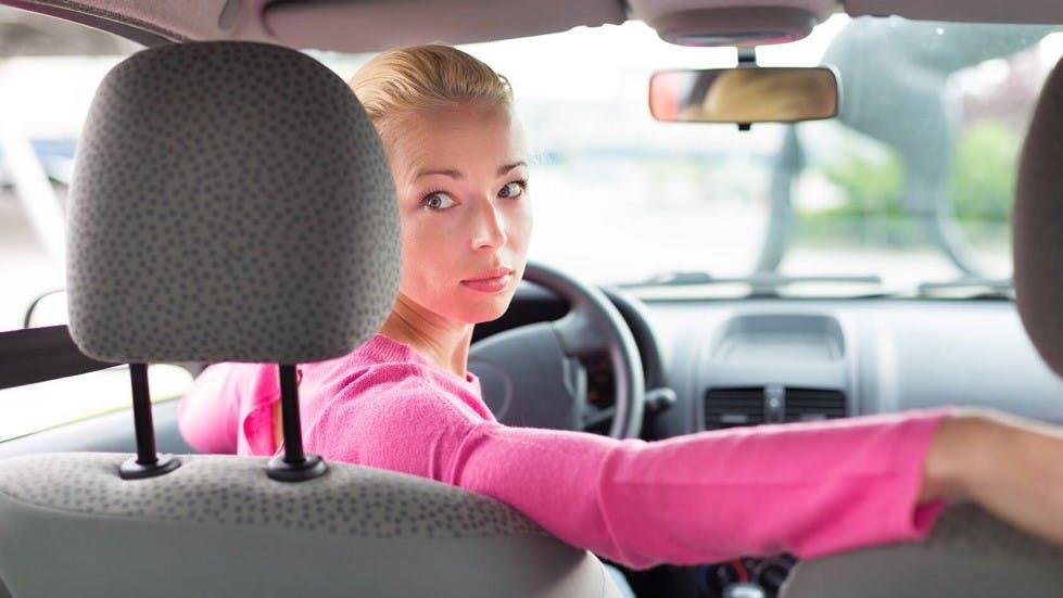 Conductrice realisant une marche arriere en voiture pour son stationnement