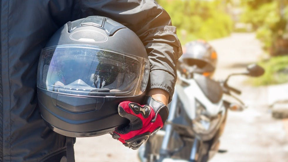 Conducteur tenant son casque de moto a la main