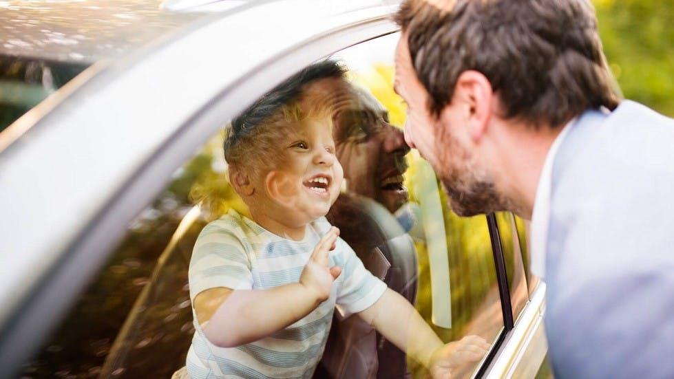 Pere et fils jouant derriere la vitre d'une automobile