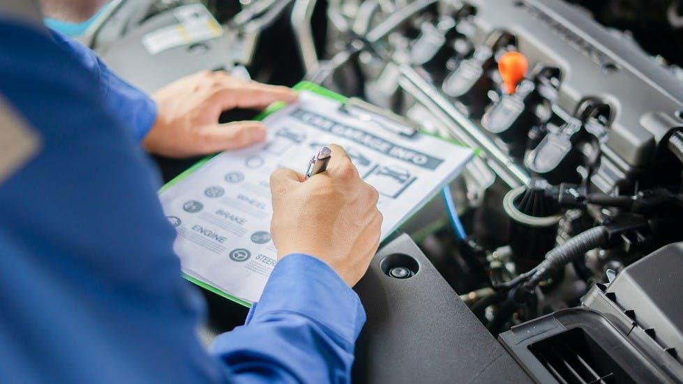 Mecanicien remplissant les informations liees a une automobile
