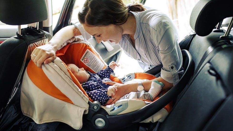 Mere de famille attachant son bebe dans un siege auto adapte