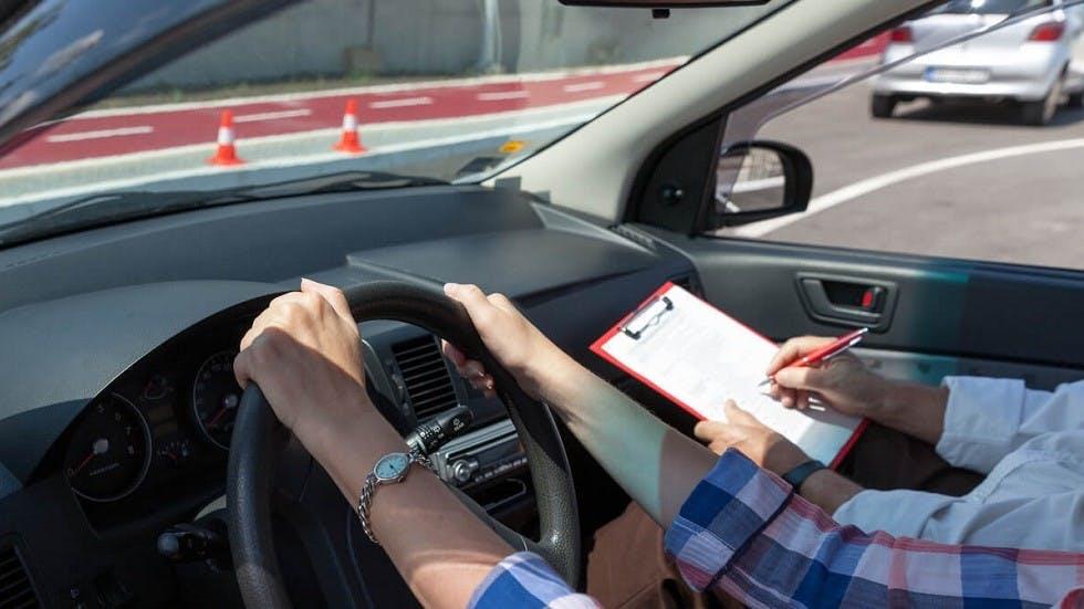 Examinateur notant une candidate a l'examen du permis de conduire